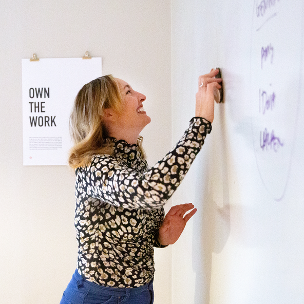 A smiling brand writer workshops her ideas on a whiteboard