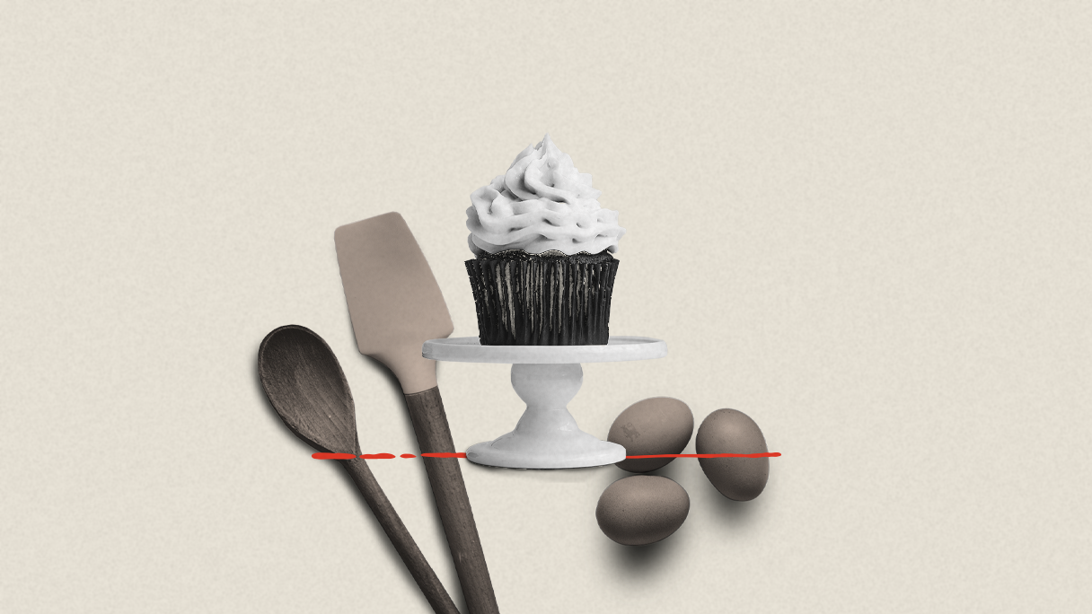 A cupcake on a serving tier with baking ingredients in the background.