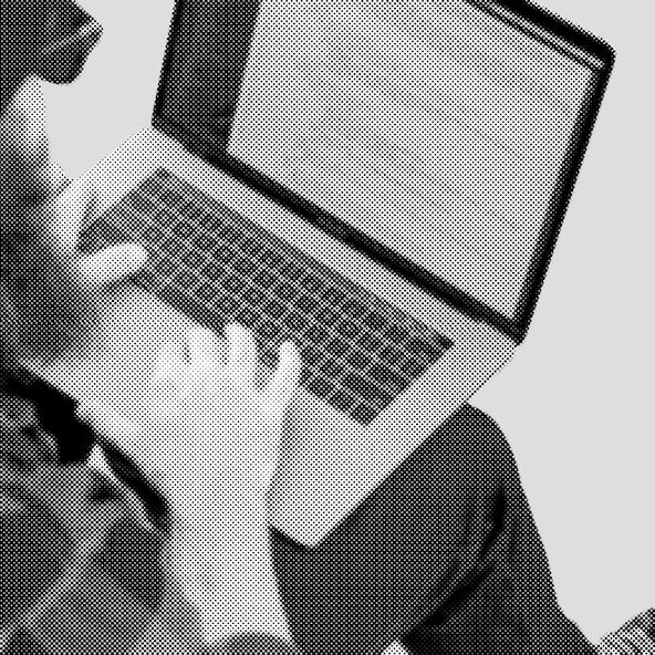 A shot over-the-shoulder of a developer working on a laptop.