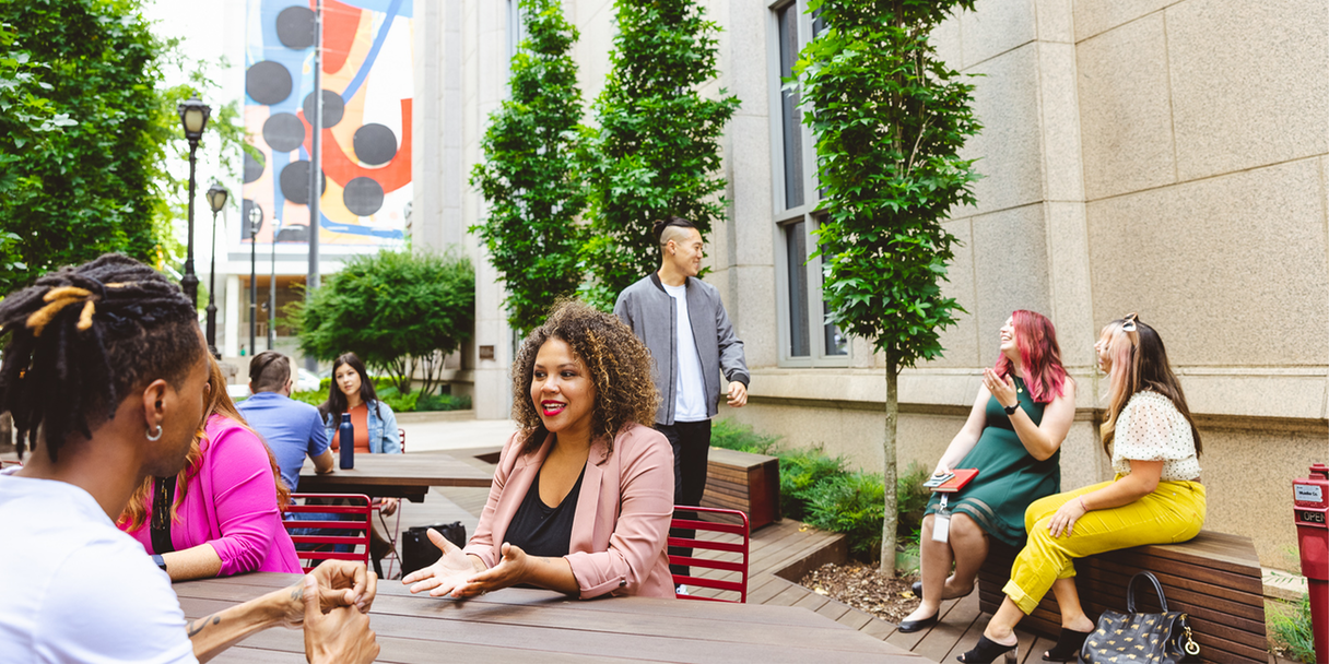 Professionals sit in an outdoor courtyard