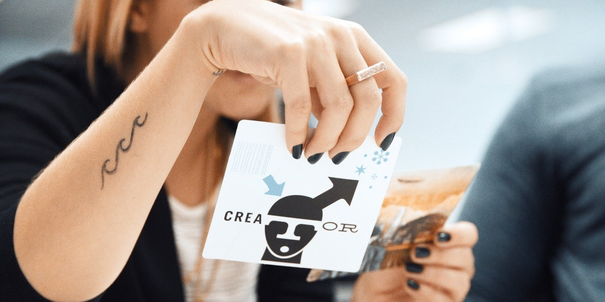 "A person holds up a card that reads ""Creator"" - a brand archetype."