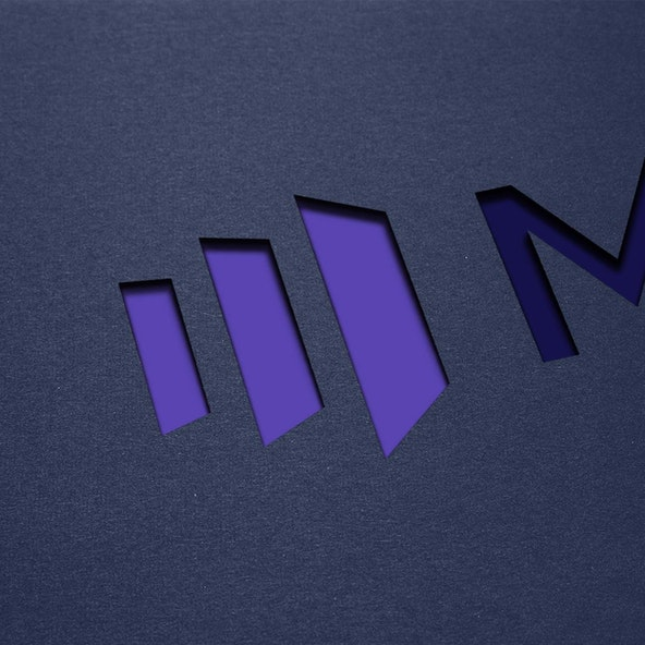 The Marketo logo diecut out of black paper.