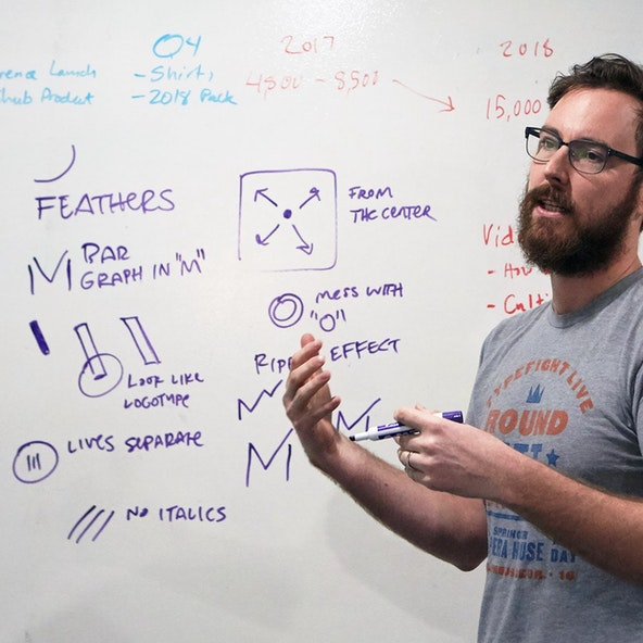 A designer talks through visual ideas in front of a whiteboard.