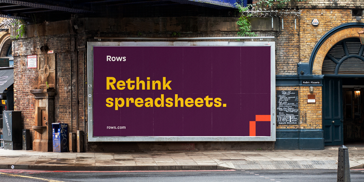 """A billboard in an urban area that reads """"Rethink spreadsheets."""""""